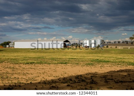 Grain silos, and a machinery shed, on a farm in the Central West region of New South Wales, Australia - stock photo