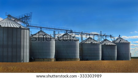 grain silos in wheat field - stock photo