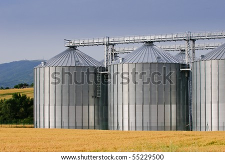 Grain store in wheat field with hills in background - stock photo