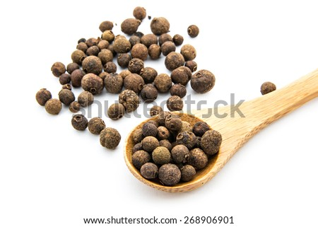 grains of allspice on wooden spoon isolated on white background - stock photo