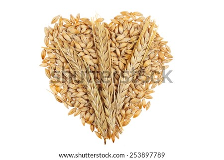 Grains of barley in the shape of a heart with three ears of barley laid on top isolated against white - stock photo