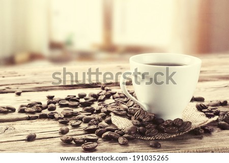 grains of brown coffee white cup and window in kitchen space  - stock photo