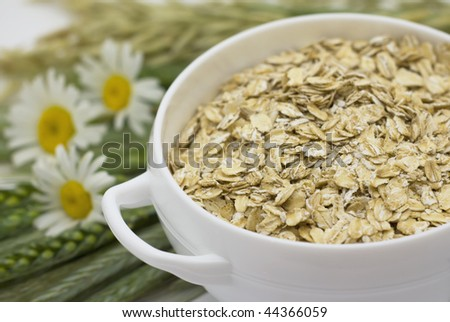 Grains of oats, camomile and  flakes in a white bowl - stock photo