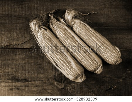 Grains of ripe corn on wooden background - stock photo