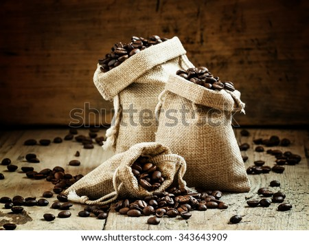 Grains of roasted coffee in bags on old wooden table in rustic style, selective focus - stock photo
