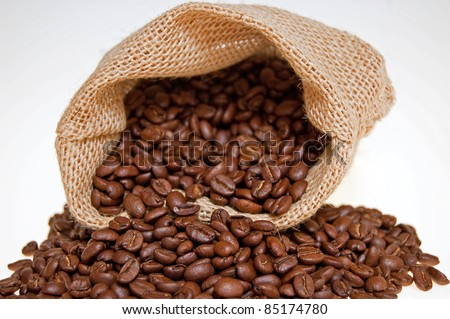 grains of the coffee spilling out from the sack on the white background