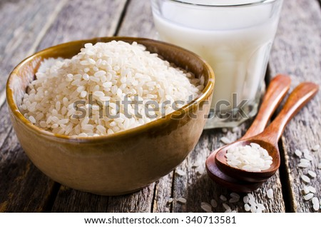 Grains of white rice in a ceramic bowl. Selective focus. - stock photo