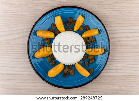 Grainy curd with raisins and slices of peach in blue glass plate on table, top view - stock photo