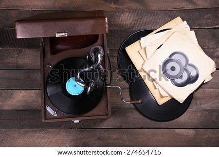 Gramophone with a vinyl record on wooden table, top view - stock photo