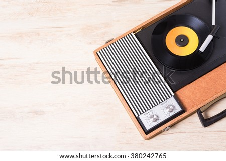 Gramophone with a vinyl record on wooden table, top view and copy space,photo desaturate and split toning for old style. - stock photo