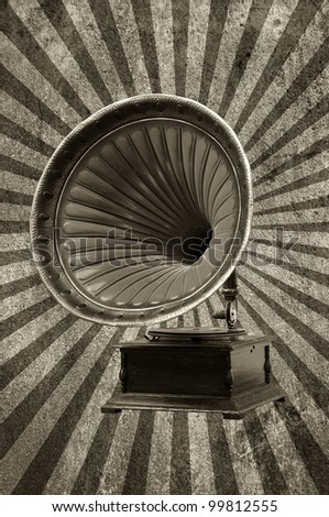 gramophone with horn speaker for playing music over a grungy background with light rays - stock photo