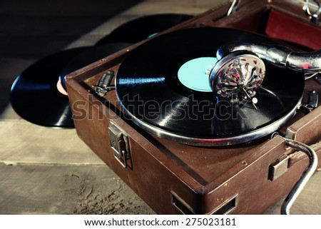 Gramophone with vinyl record on wooden table, closeup - stock photo