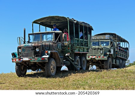 GRANADA - MARCH 19: Two military safari trucks with unidentified tourists on March 19, 2014 in Granada, Nicaragua. The military trucks are the only reliable transport in Nicaraguan rural areas.  - stock photo