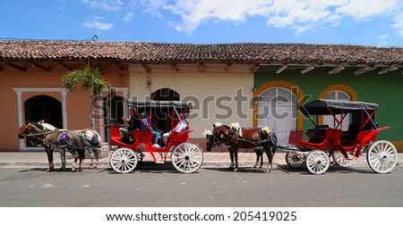 GRANADA - MARCH 19: Unidentified people at horse carts on March 19, 2014 in Granada, Nicaragua. Horse cart ride is a main tourist's attraction in Granada. - stock photo