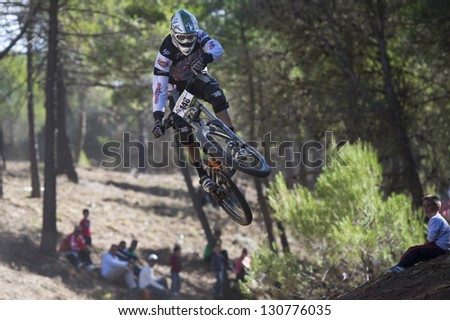 "GRANADA, SPAIN - OCTOBER 25: Unknown racer on the competition of the mountain downhill bike ""Cumbres Verdes, La Zubia"" on October 25, 2012 in Granada, Spain - stock photo"