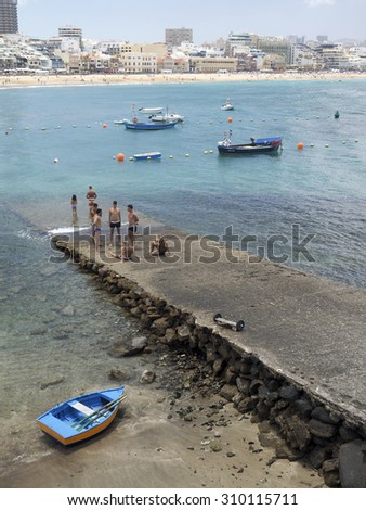 GRAND CANARY ISLAND-MAY 9: Men are seen on pier to Atlantic Ocean on Playa Las Canteras with hotels in background Las Palmas,Grand Canary Island, Spain on May 9, 2015. - stock photo