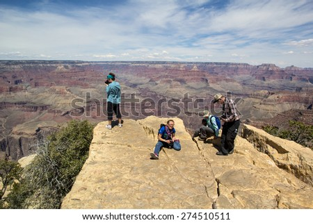 GRAND CANYON, AZ, USA-MAY 1: Tourists out on rocks viewing the Grand Canyon on May 1, 2015. Many tourists disregard the railings meant to keep people safe from falling into the canyon.