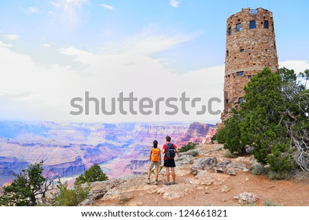 Grand Canyon people hiking. Hiker couple enoying view. Indian Desert View Watchtower, south rim of Grand Canyon, Arizona, USA - stock photo