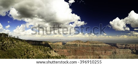 Grand Canyon, red, orange and green mountain sides under deep blue skies with whit clouds to the horizon. - stock photo