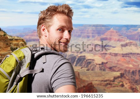 Grand Canyon travel  - Successful man mountain hiker with backpack on the top of mountains. caucasian - stock photo
