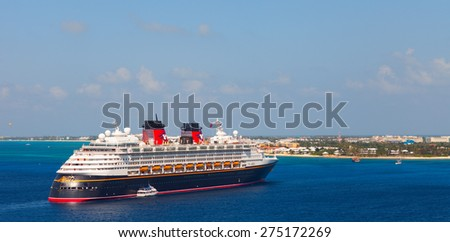 "GRAND CAYMAN, CAYMAN ISLANDS - JANUARY 24, 2012: ""Disney Magic"" cruise ship was tendered next to the shore. Over 3,000 passengers came out to visit beautiful caribbean island. - stock photo"