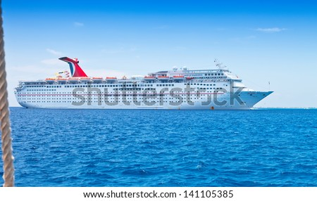 GRAND CAYMAN, CAYMAN ISLANDS - JULY 13:  Carnival Cruise Lines ship, the Inspiration, anchored off shore on July 13, 2011. It's one of the oldest Carnival ships, considered fine for short getaways. - stock photo