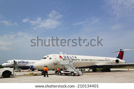 GRAND CAYMAN, CAYMAN ISLANDS - June 13  Delta Airlines McDonnell Douglas MD-80  and JetBlue Airbus A320 at Owen Roberts International Airport at Grand Cayman on June 13, 2014 - stock photo