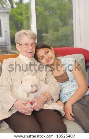 Grand daughter and grand mother with pet dog sitting on couch in sun room - stock photo