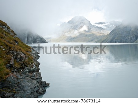 grand dixence dam view to alpine landscape on the lake - stock photo