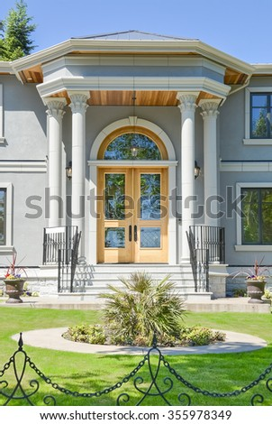 Grand entrance of brand new beautiful family house in suburban of Vancouver. House for sale. Stylish residential house with wooden door and big front yard.  - stock photo