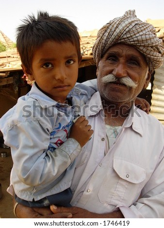 grand father holding his grand son in his arms in a village in india
