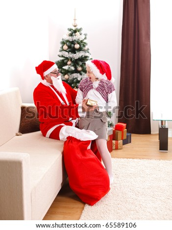 Grand father in Santa Claus uniform, giving a gift to a teenager girl