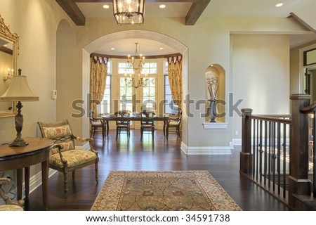 Grand foyer with area rug and view to dining room - stock photo
