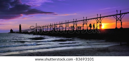 """Grand Haven Lighthouse  """"Sunset silhouette""""  Dozens of people line the Grand Haven Lighthouse pier , watching this beautiful sunset. - stock photo"""