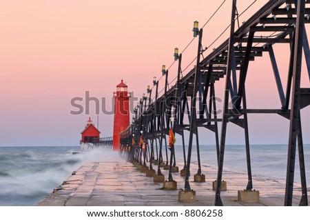 Grand Haven, Michigan Lighthouse at dawn with splashing waves, Lake Michigan, USA - stock photo