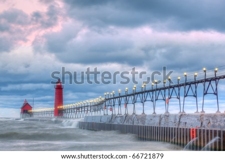 Grand Haven, Michigan Lighthouse at dawn with surf flowing over pier, Lake Michigan, USA - stock photo