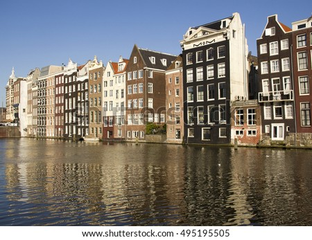 Grand historical buildings and reflections along the Damrak canal in Amsterdam, Holland