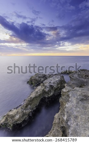 Grand majestic rocks on the shore silky ocean at sunset - stock photo