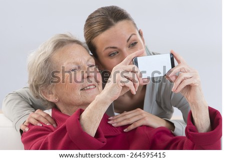 Grand-Mother and attractive young grand-daughter photographing themselves by mobile phone, smiling happily. - stock photo