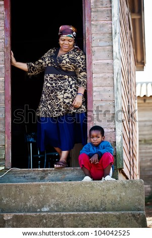 Grand mother and her son together on the porch of their house. - stock photo