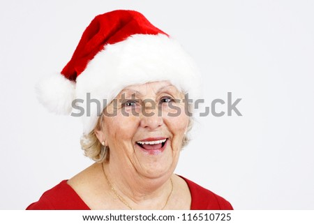 Grand-mother or elderly woman with big happy smile wearing Santa Claus hat; perfect for Christmas and seniors themes