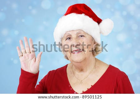 Grand-mother sending her love for Christmas by waving her hand while wearing Santa Claus hat over winter blue background - stock photo