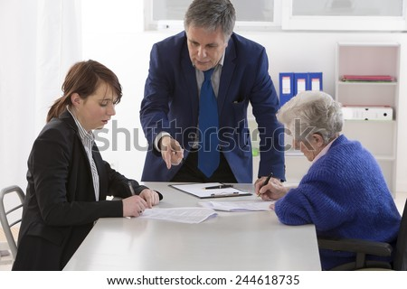 Grand mother signing insurance contract and donation to her grand daughter  - stock photo