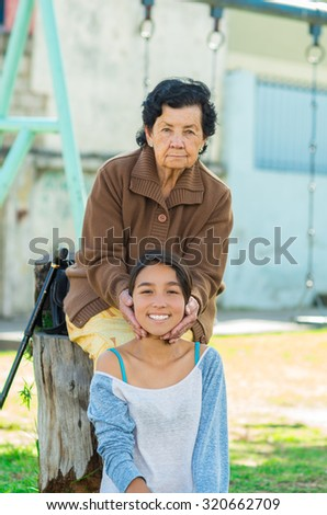 Grand mother standing behind granddaughter touching her head enjoying each others company. - stock photo