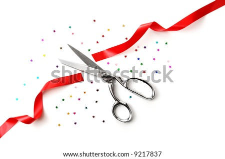 Grand Opening illustrated with a scissors, a red ribbon and confetti on a white background - stock photo