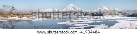 grand panorama of beautiful winter landscape with volcano and lake - stock photo