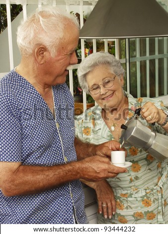 Grand parents drinking coffee at kitchen. - stock photo