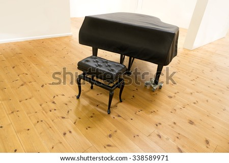 Grand piano and stool in sparse room with white walls and wooden floor - stock photo
