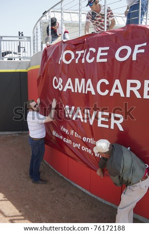 GRAND PRAIRIE, TEXAS - APRIL 15: Volunteers hang a long banner along the outfield wall of QuikTrip Park before the Lone Star Tea Party on April 15, 2011 in Grand Prairie, Texas. - stock photo