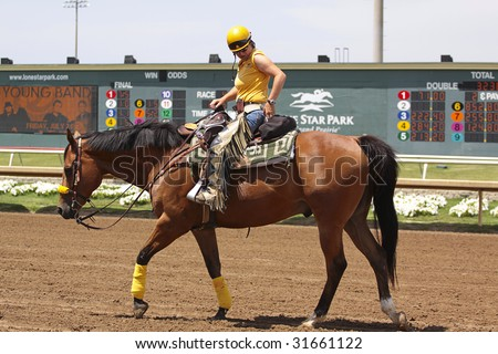 GRAND PRAIRIE,TX - JUNE 6th: A horse trainer is riding back after race at Lone Star Park Horse Race June 6th, 2009 in Grand Prairie, Texas. - stock photo